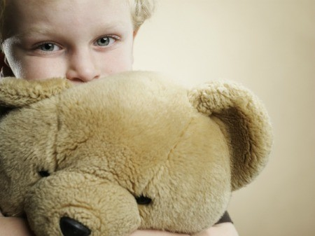 Child sniffing and hugging large stuffed bear