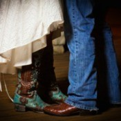 Feet and legs of groom in cowboy boots and bluejeans and bride in wedding dress and boots