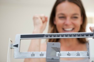 Excited woman weighing herself.