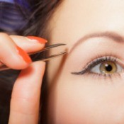 Close up of woman with thin eyebrows plucking them