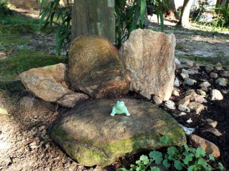 """little green frog statue on stone """"throne"""""""