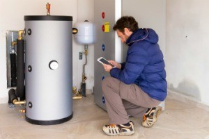 Man looking at water heater in garage
