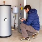 Man looking at water heater in garage