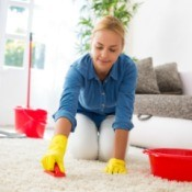 Woman on hands and knees scrubbing white carpet