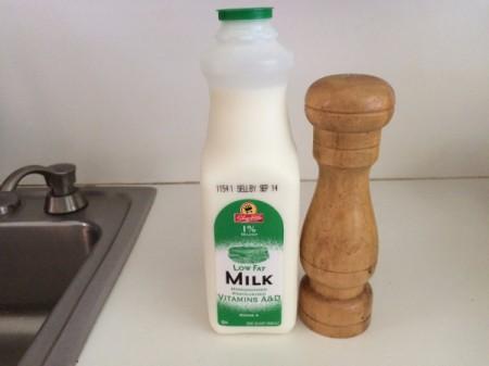 A bottle of milk next to a salt shaker.