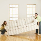 Man and woman carrying a large couch