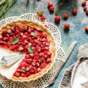 Strawberry Pie with several pieces missing surrounded by ripe strawberries