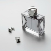 Bottle of men's cologne and cufflinks on a white surface
