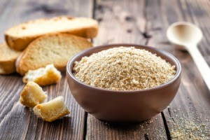 Bowl of bread crumbs surrounded by old bread