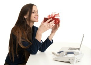 Woman at office desk holding a gift