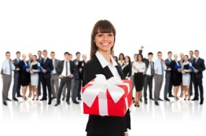 Woman in office attire holding out a wrapped gift with a row of people in suits in the background