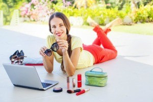 Woman lying on her belly in front of a laptop surrounded by cosmetics