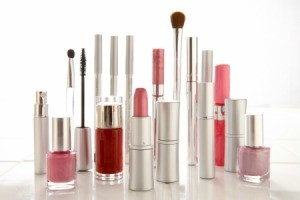 Tubes and bottles of makeup standing upright against a white background