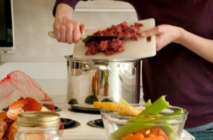 Woman pushing cubes of beef from cutting board into a soup pot with vegetables in the foreground.
