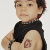 """Child dressed as a """"biker"""" with a temporary tattoo"""