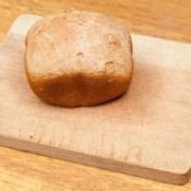 Loaf of bread machine bread that has not risen on a cutting board.