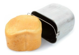 White loaf of bread machine bread laying next to a bread machine pan