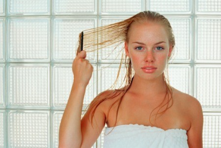 Woman in towel combing wet blond hair