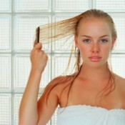 Woman in towel combing wet blond hair