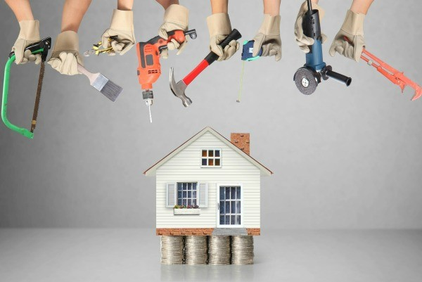 Small House Resting On Stacks Of Coins Surrounded By Hands Holding Tools  Used For Home Repairs