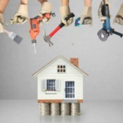 Small house resting on stacks of coins surrounded by hands holding tools used for home repairs.