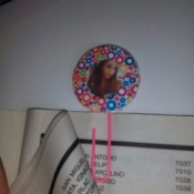 A colorful circular paper photo frame bookmark on page of book.