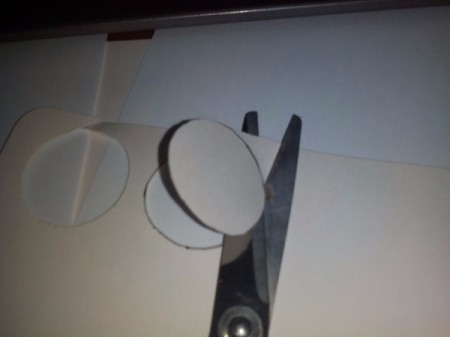 Cutting out back of frame with scissors.