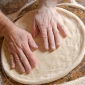 hands patting out pizza dough