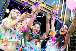 Teen girls throwing bright confetti outside