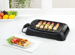 Electric table top grill with Kabobs on it