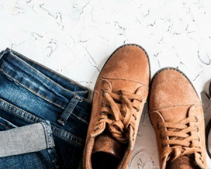 A pair of suede boots next to a pair of folded jeans