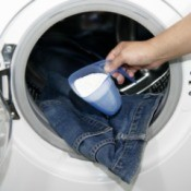 Powdered detergent being placed in front loader washing machine with jeans