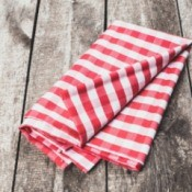 Folded Oilcloth style table cloth on a wooden table.