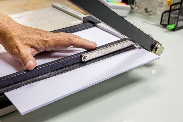 Close Of Up A Paper Cutter Being Used To Cut