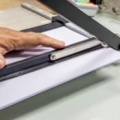 Close of up of a paper cutter being used to cut paper