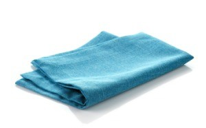 Folded blue cloth napkin on white background