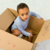 Young boy in diapers drawing on the inside of a box with a crayon
