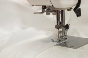 Close up of a sewing machine foot sewing white chiffon fabric