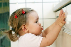 Toddler pressing up against the front of a dishwasher