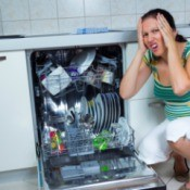 Woman making shocked face as she squats down next to open dishwasher