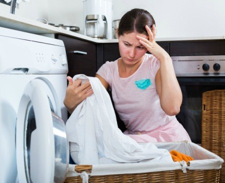 Concerned looking woman checking clean laundry for stains