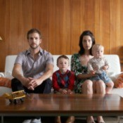 Family posed on sofa in front of wall with wood paneling