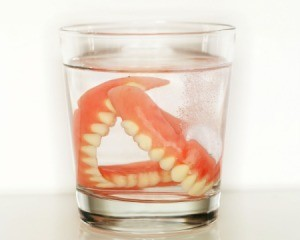 Pair of dentures in a glass of clear liquid