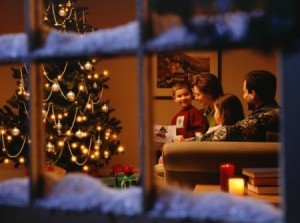 Looking in a snow dusted window at a family reading by the Christmas tree.