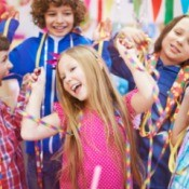 6 year old girl surrounded by friends with streamers, party blowers, and party hats