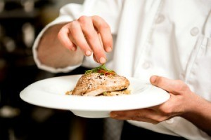 Chef sprinkling seasoning on a cooked tuna steak
