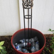 Flower pot filled part way with plastic bottles and with a wrought iron trellis in the center.