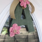 "A green letter ""A"" with pink flowers decorating a door."