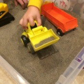 Indoor Sandbox - child's hand playing with bulldozer