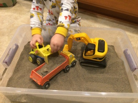 Indoor Sandbox - child playing with trucks in sandbox